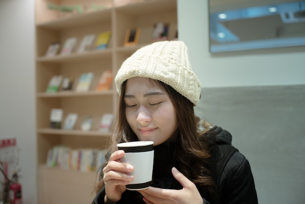 Portrait of beautiful young woman drink and smell coffee at home