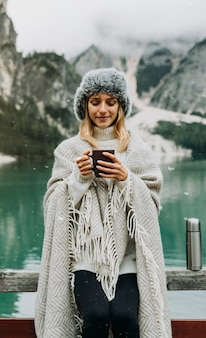 Portrait of a beautiful young woman drinking holding hot coffee cup visiting an alpine lake at braies italy.