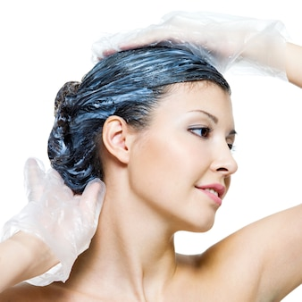 Portrait of beautiful young woman dyeing hairs isolated on white