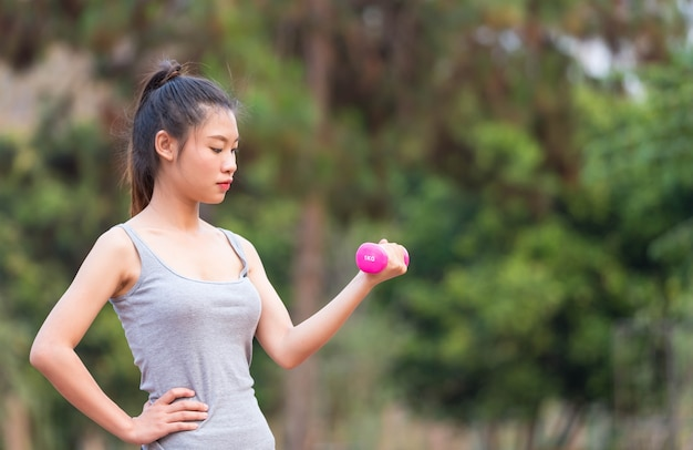 Portrait of beautiful young woman exercising in the park