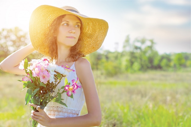 Portrait of beautiful young woman in fashionable hat holding bouquet of pink and white flowers. romantic girl in white dress is walking and dreaming on spacious field at sunset. provence style.