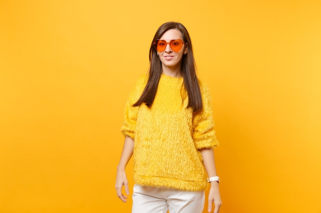 Portrait of beautiful young woman in fur sweater, white pants and heart orange glasses standing isolated on bright yellow background. people sincere emotions, lifestyle concept. advertising area.