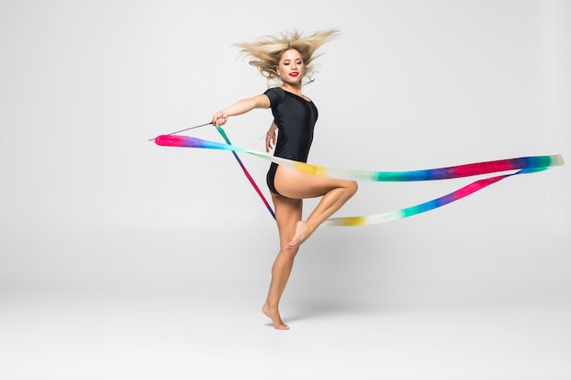 The portrait of beautiful young woman gymnast training calilisthenics exercise with ribbon. art gymnastics concept.