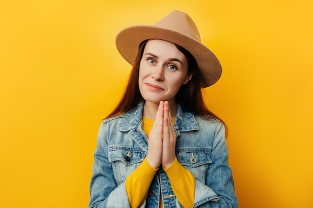 Portrait of beautiful young woman in hat isolated on yellow background joining hands in praying gesture with hope, pretty cute girl asking help and support, looking at camera, wears denim jacket