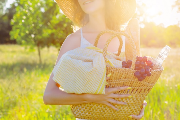 Portrait of beautiful young woman holding basket with bottle of water, baguette and grape for picnic. romantic girl in white dress and fashionable hat is smiling on field at sunset. provence style.