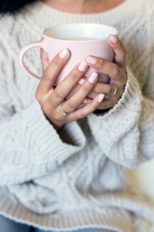 Portrait of a beautiful young woman holding a cup of hot coffee