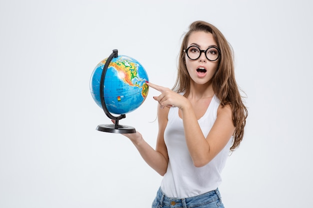 Portrait of a beautiful young woman holding globe isolated on a white background