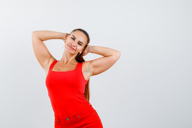 Portrait of beautiful young woman holding hands behind head in red tank top, pants and looking relaxed front view