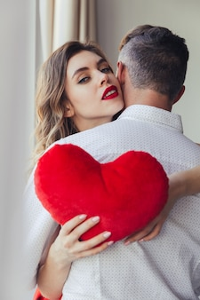 Portrait of a beautiful young woman holding her boyfriend, valentines day concept