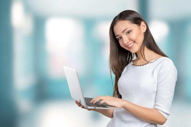 Portrait of beautiful young woman holding laptop isolated