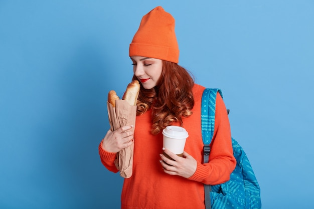 Portrait of beautiful young woman holding paper bag with bread and take away coffee