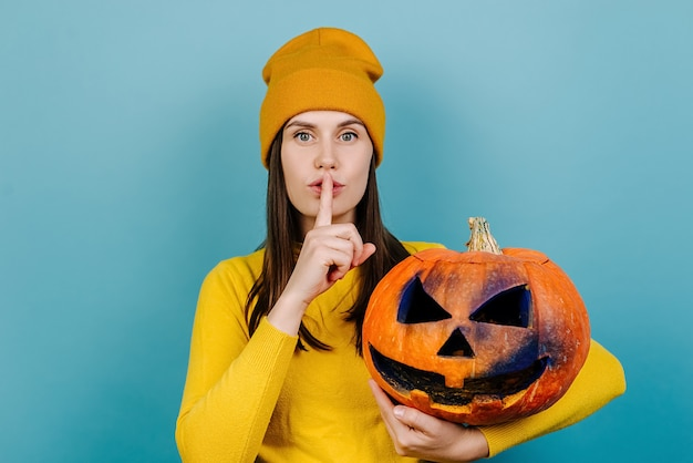 Portrait of beautiful young woman holding spooky pumpkin