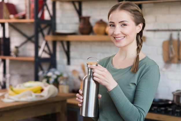 Portrait of beautiful young woman holding thermos