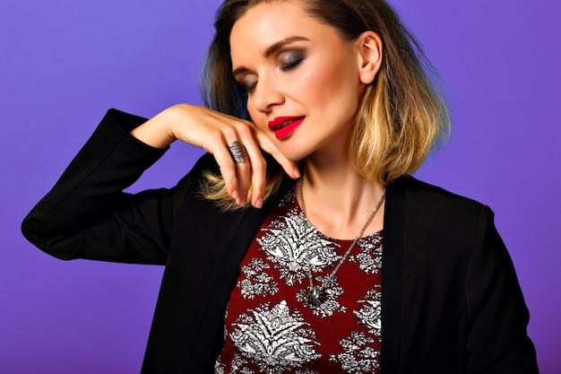 紫色の背景で隔離のカメラを探しているスタイリッシュな髪型で、黒いジャケットの美しい若い女性の肖像画。