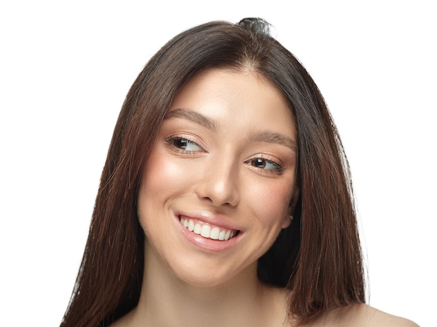 Portrait of beautiful young woman isolated on white wall. caucasian healthy female model looking at side, smiles pretty. concept of women's health and beauty, self-care, body, skin care.
