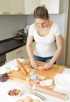 Portrait of beautiful young woman making dough on kitchen at home