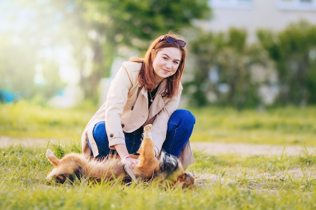 Portrait of a beautiful young woman playing with a dog in the park in the summer.