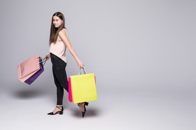 Portrait of a beautiful young woman posing with shopping bags isolated on white wall