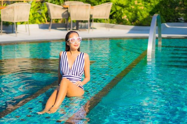 세로 아름 다운 젊은 여자는 리조트 호텔에서 수영장 주변 휴가에 미소 레저를 휴식