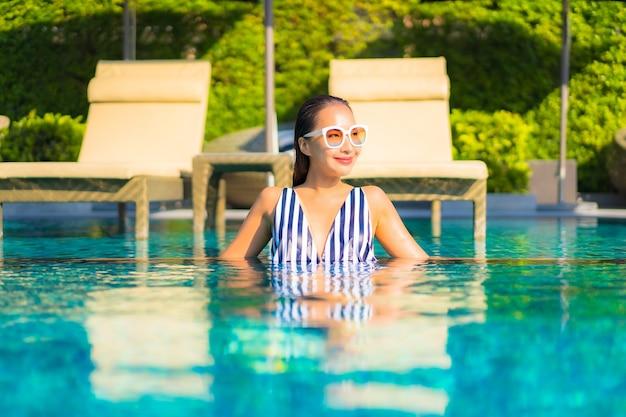 Портрет красивой молодой женщины расслабляет отдых улыбкой на отдыхе вокруг бассейна в курортном отеле
