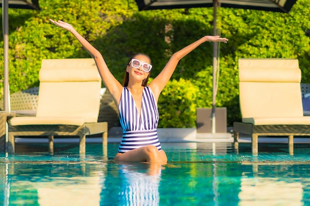 Portrait beautiful young woman relax smile leisure on vacation around swimming pool in resort hotel
