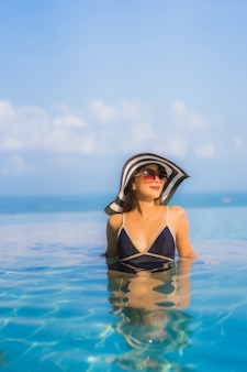 Portrait of beautiful young woman relaxing around swimming pool in hotel resort