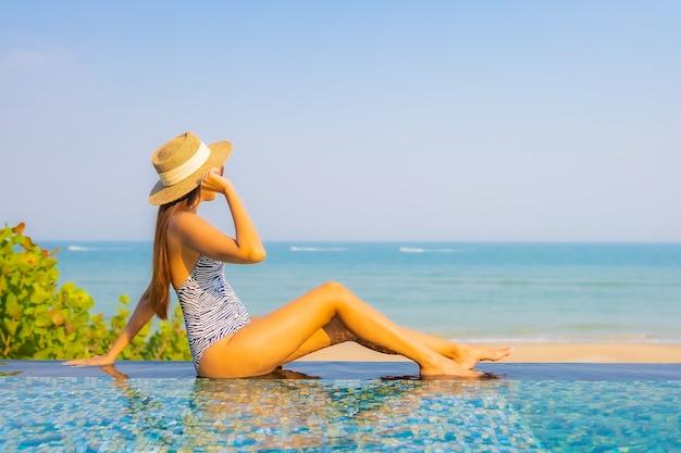 Ritratto di bella giovane donna che si distende sulla piscina