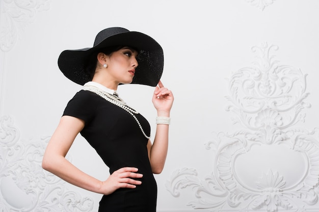 Portrait of a beautiful young woman in retro style in an elegant black hat and dress over luxury rococco white wall