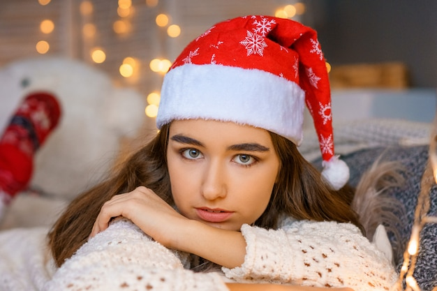 Portrait of beautiful young woman in santa claus hat on bokeh background