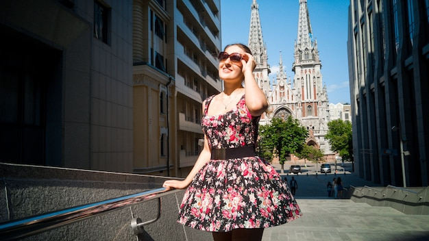 Portrait of beautiful young woman in short dress and sunglasses posing on city stret against old catholic cathedral