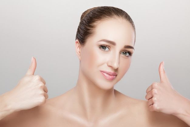 Portrait of beautiful young woman showing gesture thumbs up on a gray background