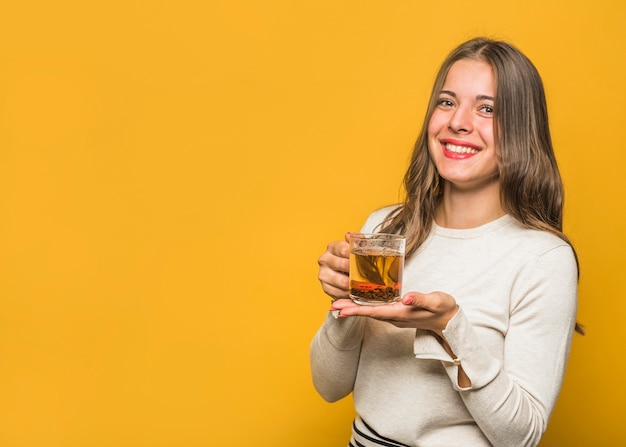 Portrait of a beautiful young woman showing herbal tea glass cup against yellow background