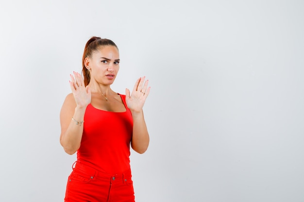 Ritratto di bella giovane donna che mostra gesto di resa in canottiera rossa, pantaloni e vista frontale spaventata