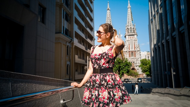 Portrait of beautiful young woman sightseeing old european town with ancient cathedral