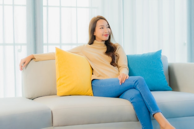 Portrait of beautiful young woman on sofa in living room