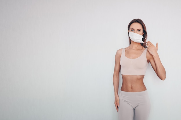 Portrait of beautiful young woman in sportswear wearing protective mask
