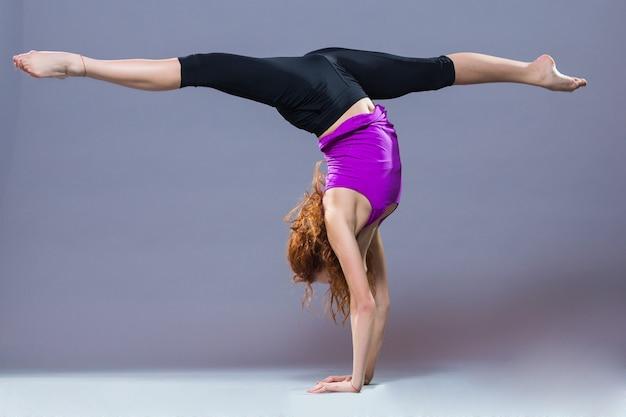 Ritratto di abbigliamento sportivo giovane e bella donna che lavora in uno sfondo grigio. ragazza sportiva adatta che fa yoga avanzato, pilates, fitness.