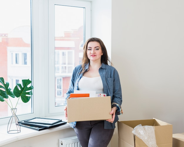 Portrait of beautiful young woman unpacking cardboard boxes at her new home