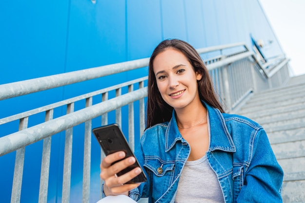 Portrait of a beautiful young woman using the mobile phone on the stairs on the street with blue background