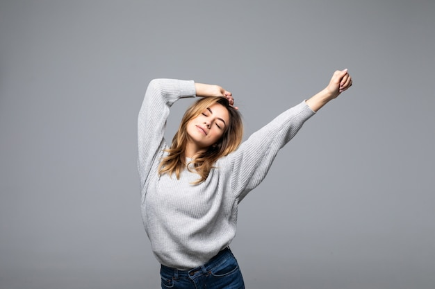 Portrait of a beautiful young woman wear in sweater keeping her arms raised standing against grey wall
