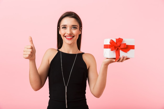 Portrait of a beautiful young woman wearing black dress standing isolated over pink background, holding gift box, giving thumbs up