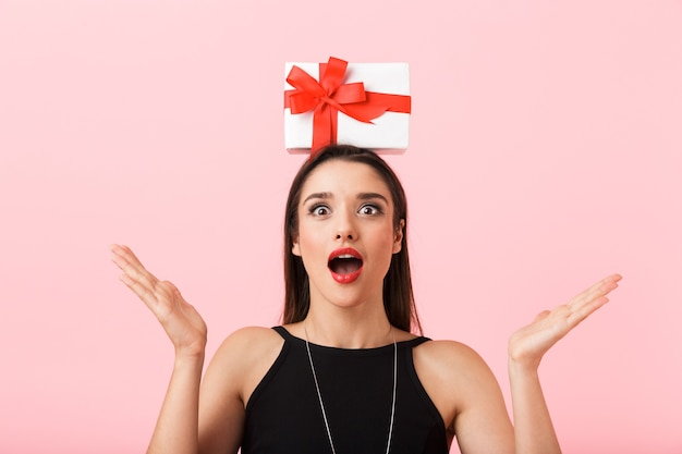 Portrait of a beautiful young woman wearing black dress standing isolated over pink background, holding gift box on her head