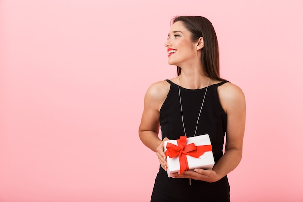Portrait of a beautiful young woman wearing black dress standing isolated over pink background, holding gift box, looking away