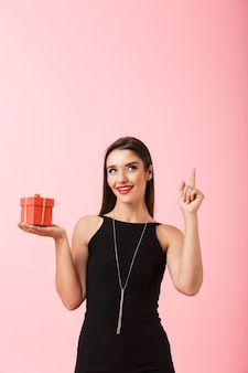 Portrait of a beautiful young woman wearing black dress standing isolated over pink background, holding gift box, pointing finger up