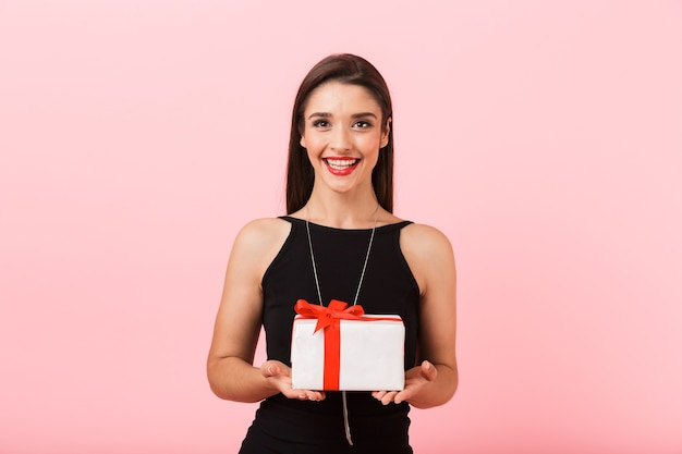 Portrait of a beautiful young woman wearing black dress standing isolated over pink background, holding gift box