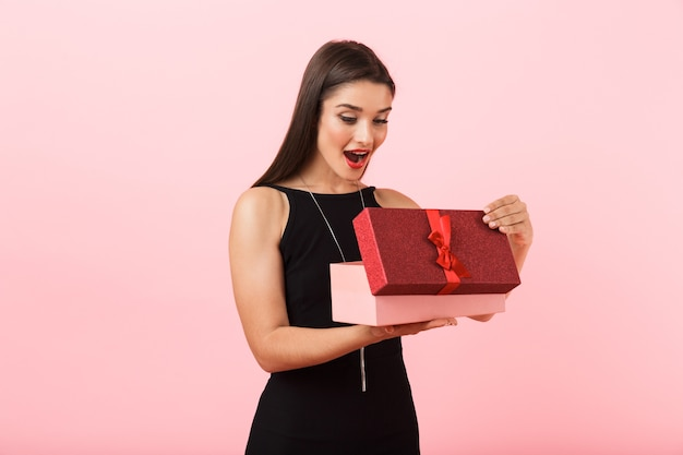 Portrait of a beautiful young woman wearing black dress standing isolated over pink background, open gift box