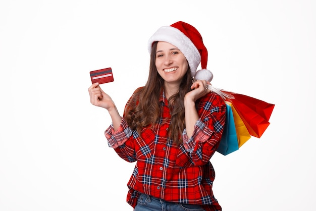 Portrait beautiful young woman wearing christmas santa hat with shopping bags and credit card