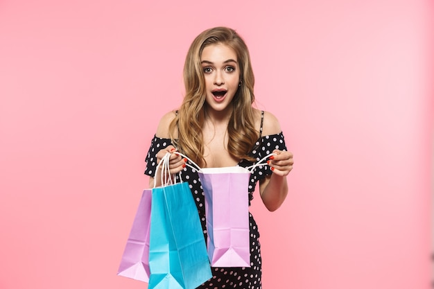 Portrait of a beautiful young woman wearing dress standing isolated over pink wall, carrying shopping bags