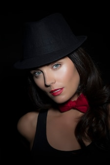 Portrait of beautiful young woman wearing tophat and bow-tie on black background