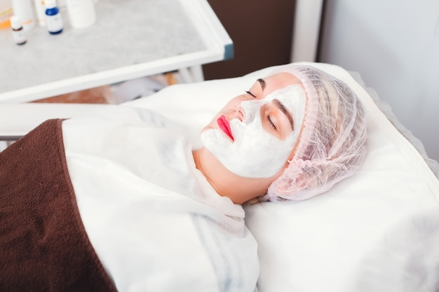 Portrait of beautiful young woman which applying facial mask.  cosmetic procedure in spa salon. face skin care.